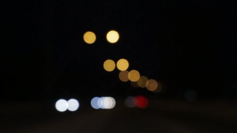 Driving at night. Windshield view of car lights in the darkness. Defocused traffic lights on town street. Abstract background