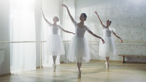 Three Young and Gorgeous Ballerinas Synchronously Dancing. They Wear White Tutu Dresses. Shot on a Sunny Morning in a Bright and Spacious Studio. Shot on RED EPIC-W 8K Helium Cinema Camera.