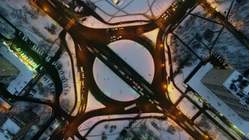 Bela Kun square with transport traffic on roundabout in winter evening. Aerial view in timelapse