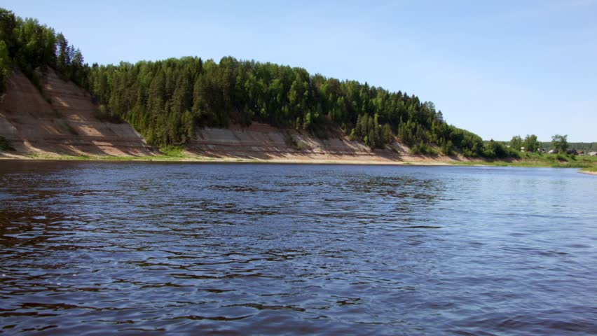 Beautiful view of forest and steep coast river in summer. Rocks of Permian outcrop on banks of river