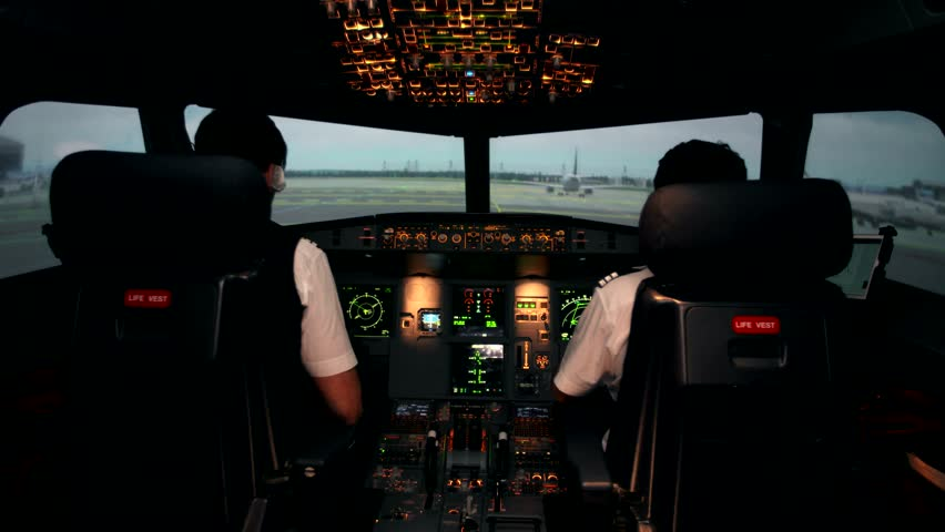 Cabin crew in the cockpit or flight deck of a passenger airplane use radio to talk with air traffic controller before taxiing on the runway and departure on plane. Ready to take off | Shutterstock HD Video #23361415