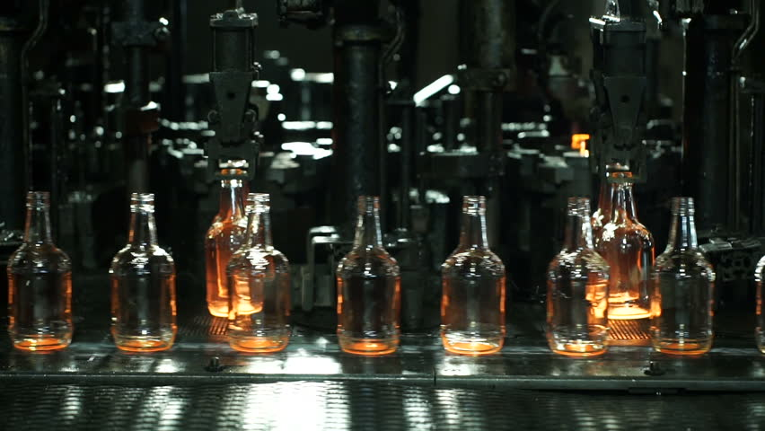 Production of glass bottles. Glass recycling. Bottle manufacturing industrial factory. Molten glass. Glass factory. Automated production line. Furnace. Recycling.