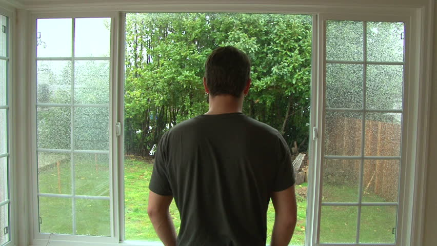 Man looking out window watching heavy wind and rain during storm.
