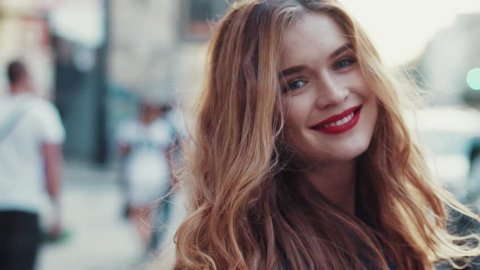 Gorgeous young woman with beautiful blue eyes and golden long hair, with a bright red lipstick. Attractive young lady is walking down the city street, turns to camera and gives a lovely playful smile.