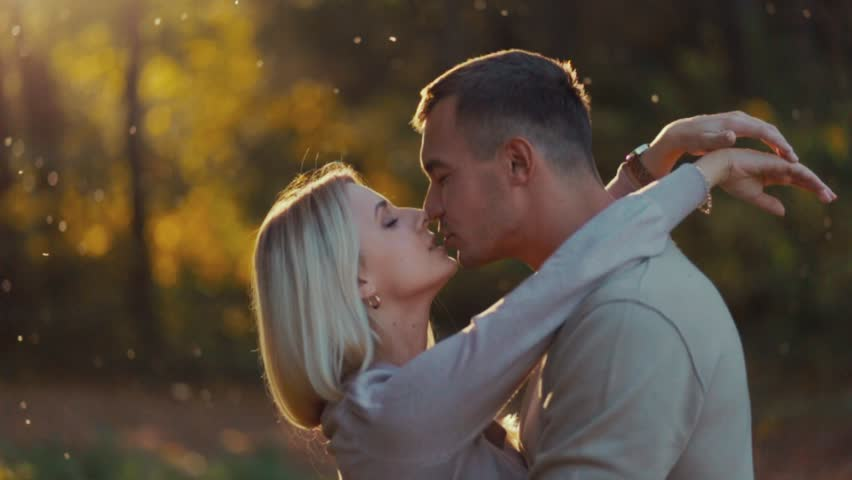 Close up view of attractive young blonde girl passionately kissing her handsome boyfriend in a warm autumn sunshine. Couple goals, romantic atmosphere. Autumn forest on the background. #23381725