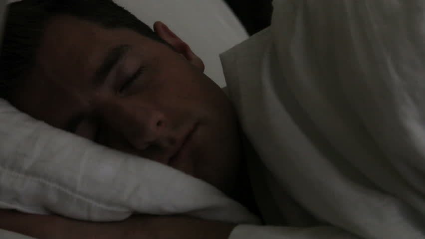 Man sleeping in bed slamming down alarm clock