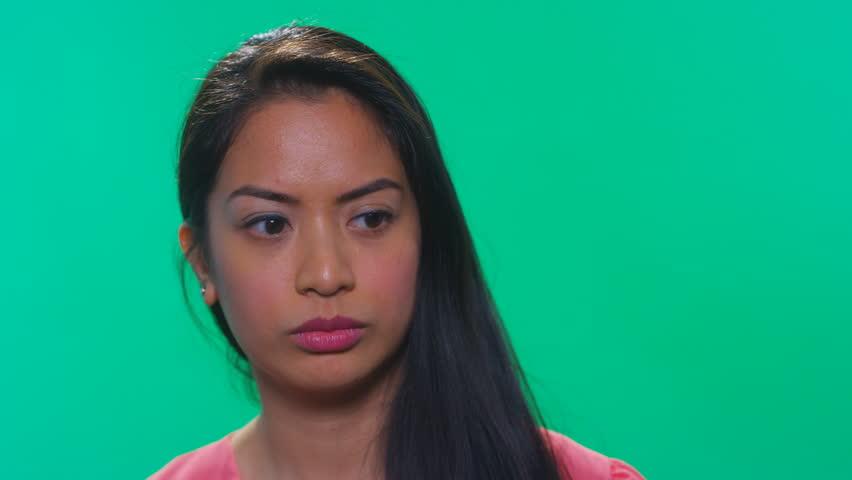 Asian woman on green background looking off screen | Shutterstock HD Video #23399515