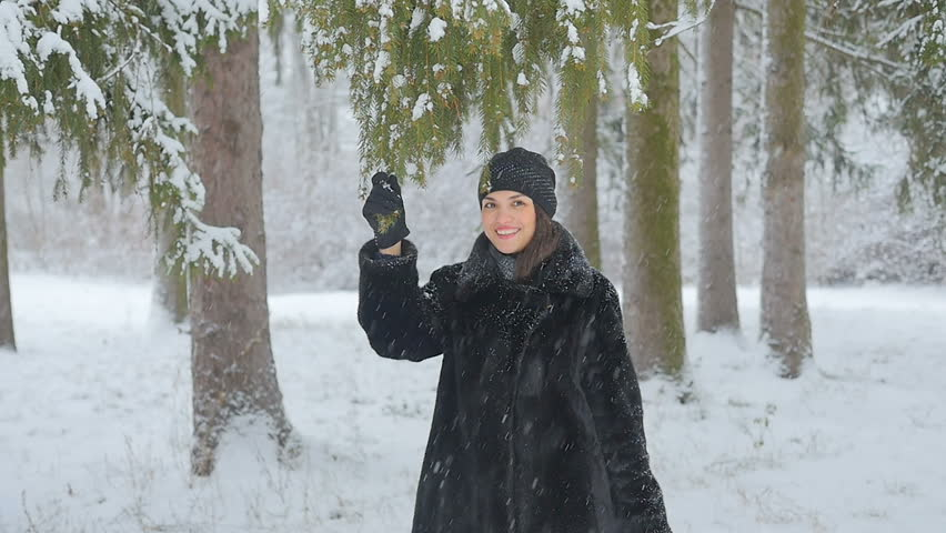 A Cheerful girl is standing under the tree and shaking off the snow. Snow is falling on her head. The face is in the snow, snow is on the head. Snowflakes are on the eyelashes. Slow motion