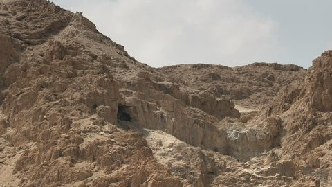zoom in on a cave in the hills at qumran where the dead sea scrolls were discovered in israel