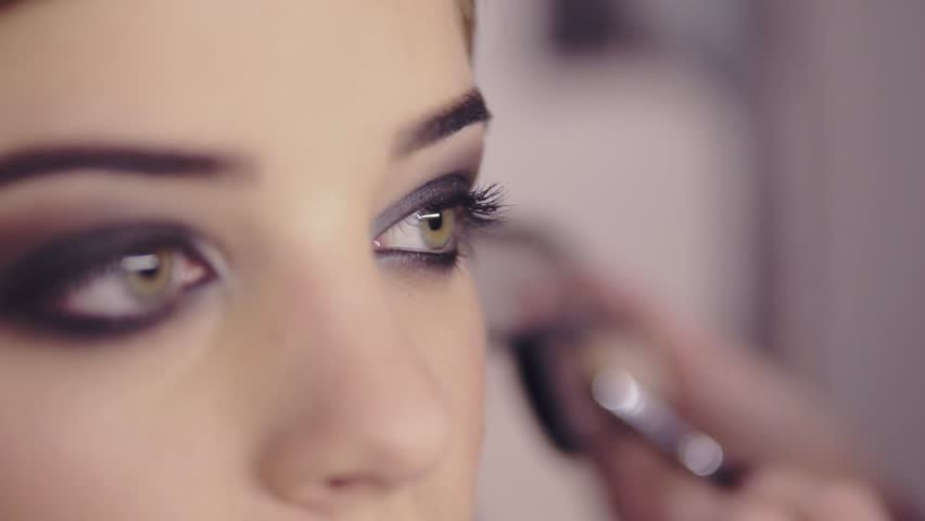 Make-up artist applying eye shadow makeup to model's eye. Close up view. Smoky eyes. Left view | Shutterstock HD Video #23425375