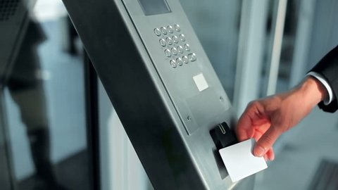 Close-up - the man put the card on checkpoint and open a door in building