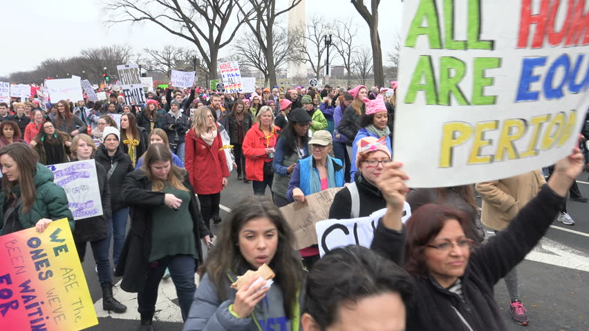 WASHINGTON, DC - JAN 21, 2017: Women's March on Washington, marchers pass Washington Monument in background, part of gigantic turnout that flooded DC in an anti-inauguration show of solidarity.