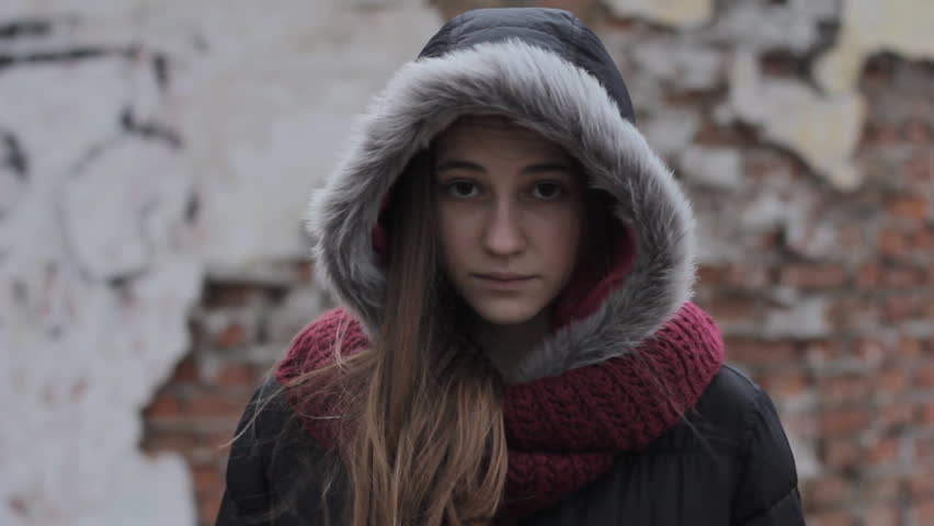 resentment, sadness, frustration: Portrait of cute girl wearing winter jacket with hood up sad looking at camera standing in front of brick wall of old building, steadicam shot #23449615