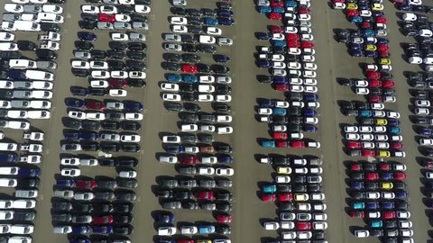 Aerial top down bird view new car storage parking lot showing imported new vehicles or ready to export new automobiles storage facility car industry for American and European market for car sales 4k