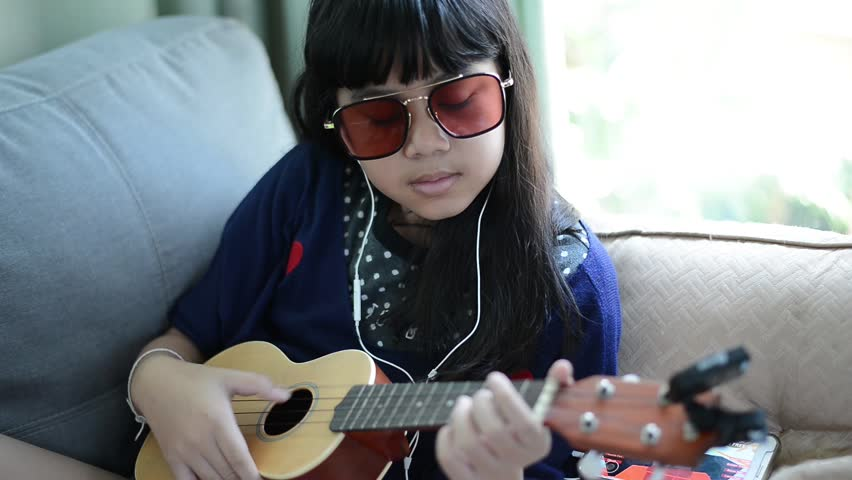 Happy smiling girl ,wearing glasses and jean jacket,learning to play the acoustic guitar,at home laying on sofa in the living room