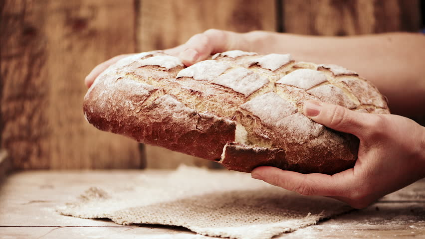 Female baker hands breaking homemade bread over wooden background.