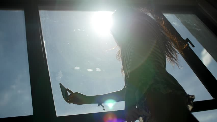 Silhouette of Young Woman Taking Selfies Next To Window in Direct Sunlight with Lens Flares, Low Angle | Shutterstock HD Video #23487325