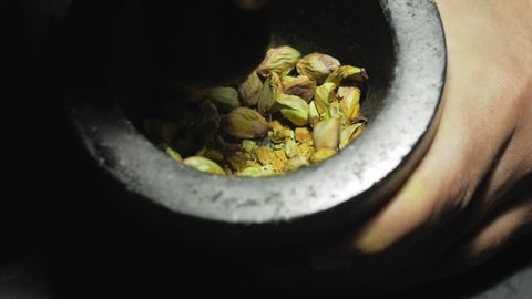 Pistachio grinding or a mortar for cakes and ice screams making. In a studio lighting, slow motion