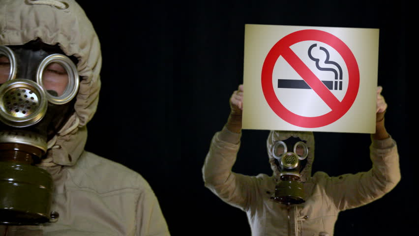 Peoples in gas mask holds anti-smoking sign