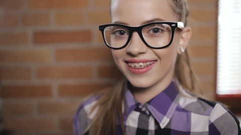 Teen girl portrait. Pupil in eyeglasses and braces.