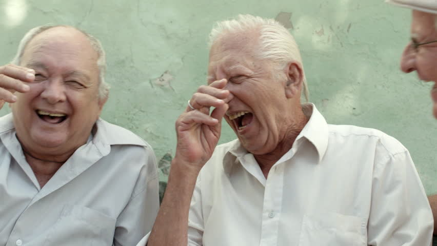 Active retirement, group of three elderly male friends talking and laughing on bench in public park