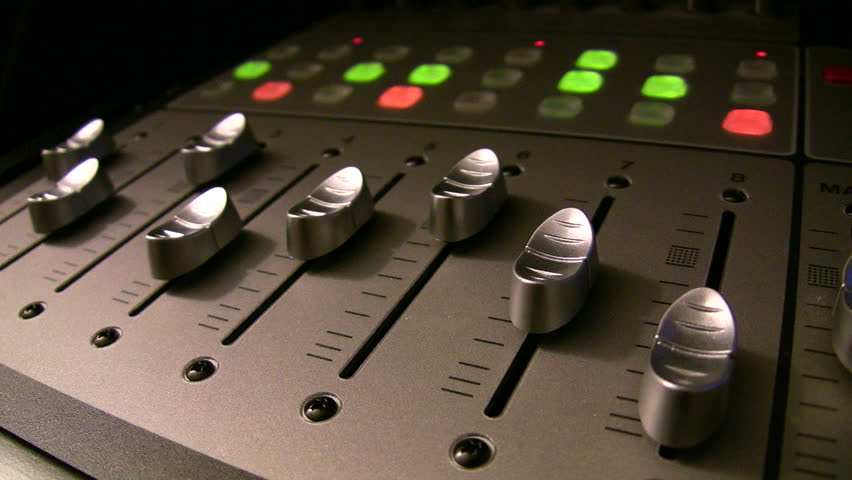 audio mixer angle in low dramatic light with motorized faders moving and lights blinking