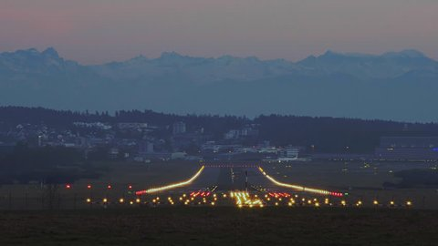 Airplane Landing At Zurich International Airport At Dusk With The Alps In Distant Background