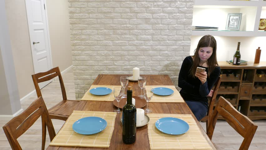 Girl in black evening dress stay alone at empty dinner table, spend time using smartphone. Four person meeting, lonely young woman tired of waiting. Guests late in coming, while she ready while ago