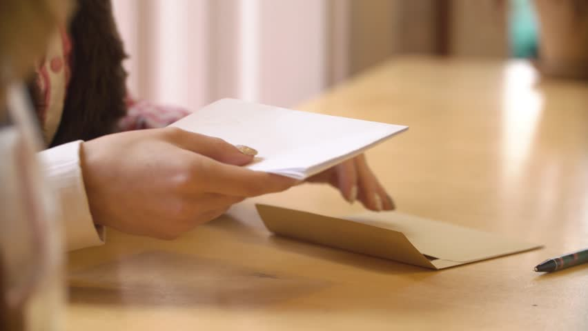 Close-up, hands beautiful girl puts a romantic letter in an envelope
