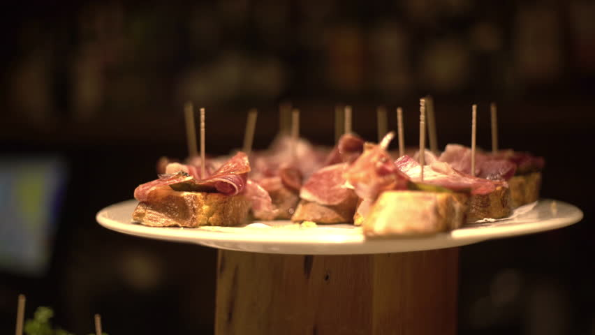 Pinchos of serrano ham in a basque bar. Bites of ham. Sandwiches of ham.