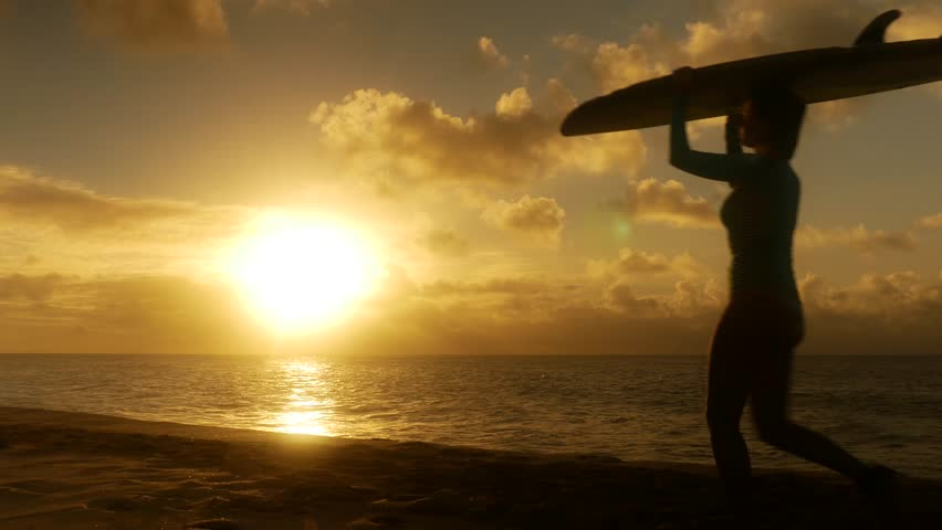 9dbc4bbef1 Surfer couple in silhouette walking with long surfboards at sunset on beach