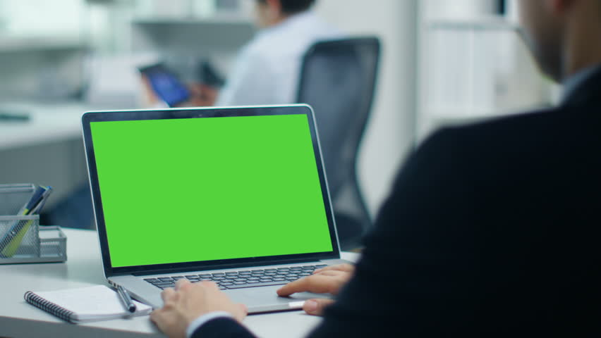 Businessman Working on a Laptop with Green Screen on. In the Background His Colleague Working on a Tablet Computer. Office is Modern and Bright. Shot on RED Cinema Camera 4K (UHD). | Shutterstock HD Video #23570839