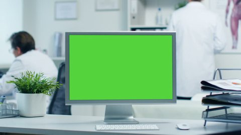 Close-up of a Monitor with Green Screen. Doctor Works with Folders, Assistant Talks with Patients on the Phone. Office is Modern and Light. Shot on RED Cinema Camera 4K (UHD).