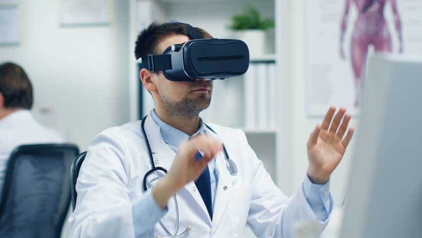 Male Doctor Conducting Experimental Medical Procedure Wearing Virtual Reality Headset. His Assistant Closely Monitors Activity from His Desk.Office is Light and Ultra-Modern. Shot on RED Cinema Camera