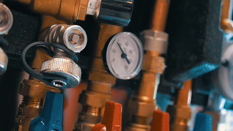 A row of red and blue water valves and pressure gauges regulating the flow of water in the different pipelines. Shot in motion. Closeup. Dolly shot