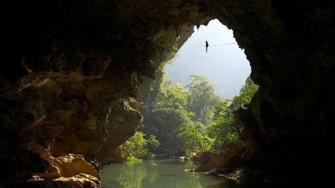 silhouette of a man walking on a highline slackline in a beautiful environment with river flowing through cave