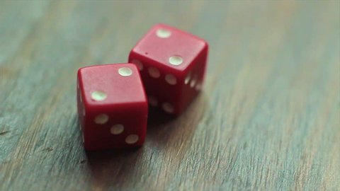 Red dice roll a pair of twos, for number four, on wooden table. Three times.