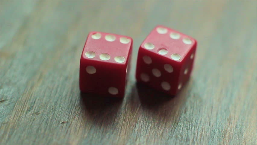 On a wooden table, two red dice roll a pair of six, for a total of twelve points. Two options of roll, critical focus.