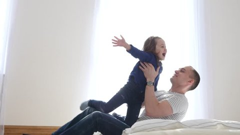 Little Child Girl Daughter Have Fun Jump To Father Arms So They Falling On A Bed