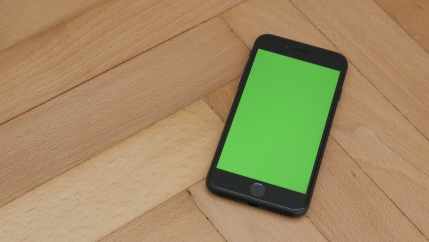 4k00:05ZAJECAR, SERBIA   NOVEMBER 2016: Close Up Of Black Phone With Green  Screen Chroma Key Display Slow Tilt On Wooden Floor