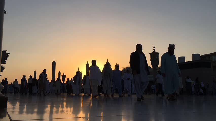 Pilgrims walking outside at haram Nabawi Mosque after dawn.