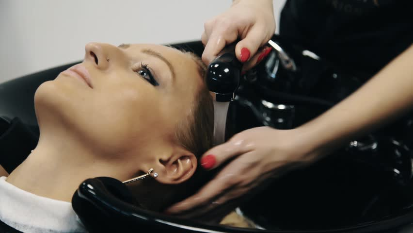 Hairdresser With Red Nail Polish Washing Blond Dyed Girl Hair Over Sink In  Beauty Saloon,