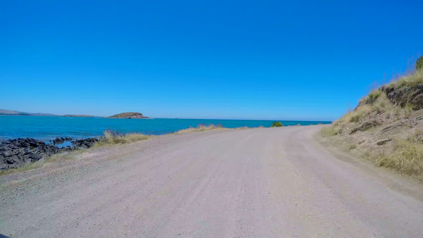 Ocean Views vehicle POV, driving along dirt road at the base The Bluff overlooking Encounter Bay at Victor Harbor, South Australia, 4k real time.