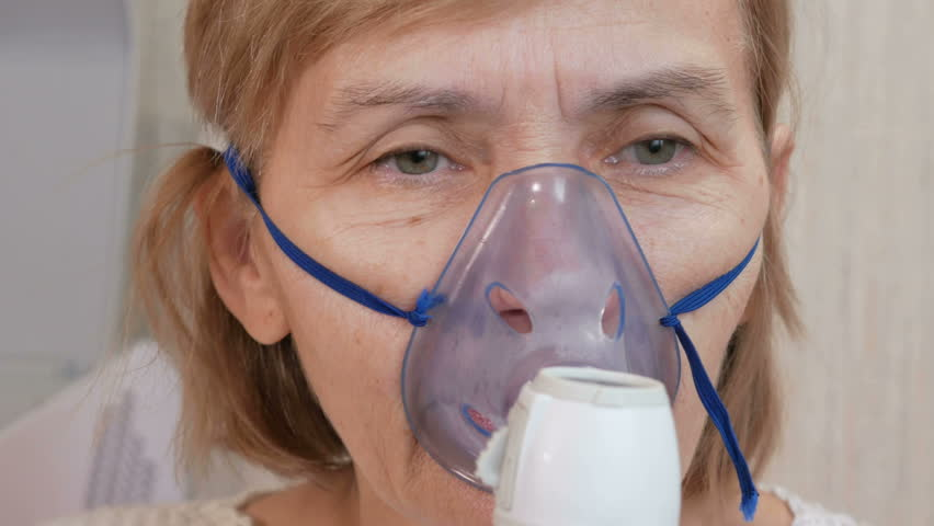 Senior woman holding a mask from an inhaler at home. Treats inflammation of the airways via nebulizer. Preventing asthma and cough