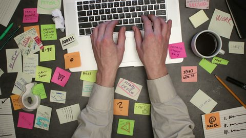 Man working on laptop computer with post it notes everywhere on his work place. Top view on businessman office desk. Stop motion animation.