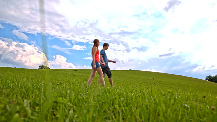 Enjoying walk on green grass barefoot wide shot.Low angle view from grass of two person in focus holding hands while walking on empty green lawn. Blue sky with clouds covering sun.