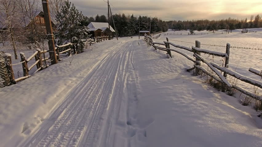 Camera moving along rural winter road near wooden fence of paddock. Sunset light. Russia   Shutterstock HD Video #23751745