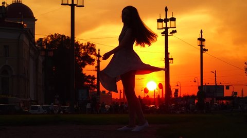 Merry young woman happily turn around in dance, short light dress skirt fly around, black silhouette against vivid orange sunset, urban place. Slow motion shot, live is good concept