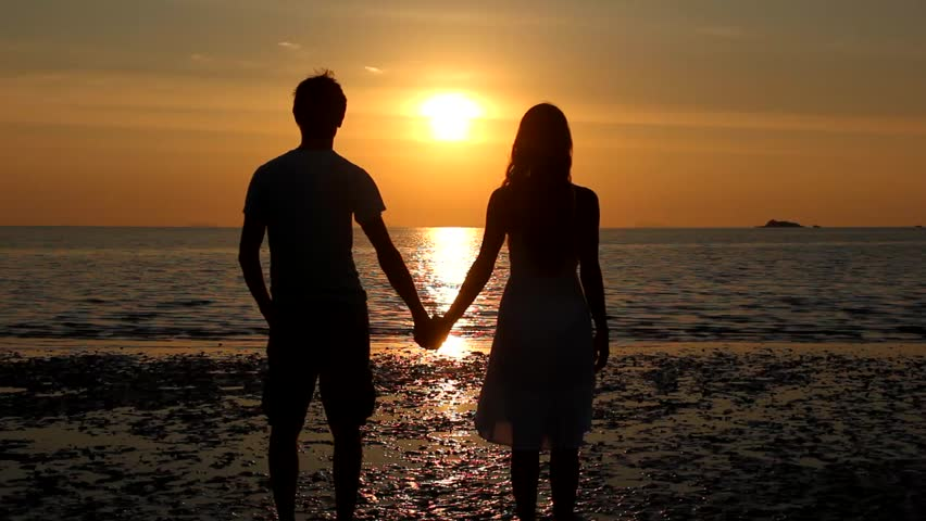 Couple silhouette staring at sunset on the beach start kissing and she lifts one leg up bending her knee in the island of Koh Phangan, Thailand. Valentine Day celebration