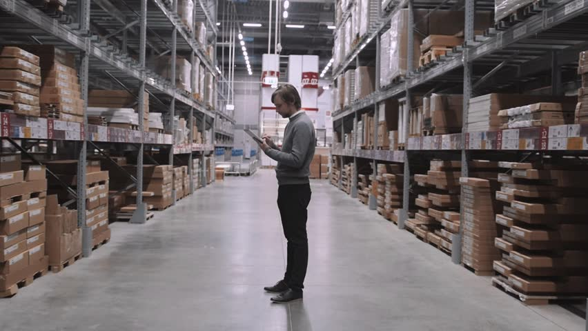 Manager With Tablet PC Checking Goods At Supermarket Warehouse. Modern Furniture Stock